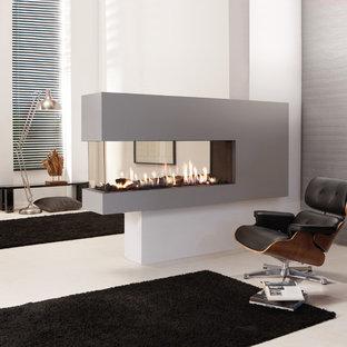 На фото: большая хозяйская спальня в стиле ретро с белыми стенами, двусторонним камином, фасадом камина из штукатурки, белым полом и бетонным полом