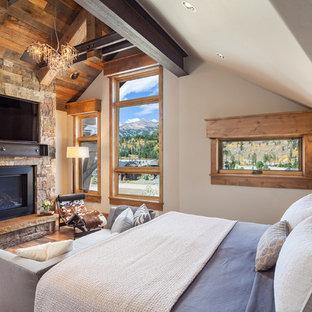 Diseño de dormitorio principal, rural, grande, con paredes marrones, suelo de madera oscura, chimenea tradicional, marco de chimenea de piedra y suelo azul