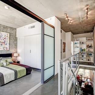 Example of a mid-sized urban loft-style concrete floor bedroom design in Seattle with gray walls and no fireplace