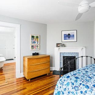 他の地域の中サイズのトランジショナルスタイルのおしゃれな主寝室 (グレーの壁、淡色無垢フローリング、コーナー設置型暖炉、タイルの暖炉まわり) のレイアウト
