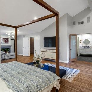 Foto de dormitorio principal, contemporáneo, extra grande, con paredes grises, suelo de madera clara, chimenea tradicional, marco de chimenea de hormigón y suelo gris