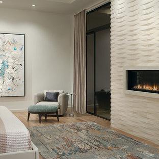 Großes Modernes Hauptschlafzimmer mit weißer Wandfarbe, hellem Holzboden, Gaskamin, Kaminumrandung aus Stein und beigem Boden in Phoenix