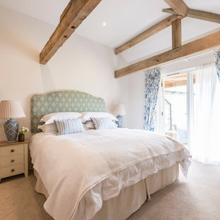 Inspiration for a large country guest bedroom in Dorset with white walls, carpet and grey floors.