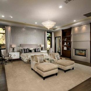 На фото: класса люкс огромные хозяйские спальни в стиле модернизм с бежевыми стенами, темным паркетным полом, стандартным камином и фасадом камина из штукатурки