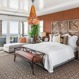 World-inspired master bedroom in San Diego with brown walls, light hardwood flooring and grey floors.