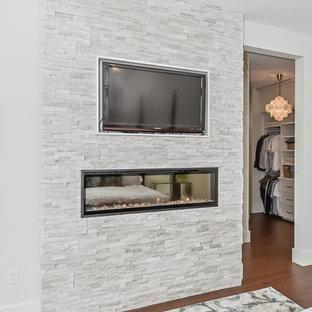Idées déco pour une chambre parentale contemporaine de taille moyenne avec un mur gris, cheminée suspendue et un manteau de cheminée en pierre.