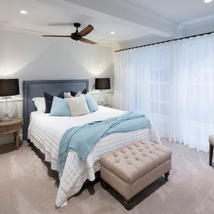 This is an example of a beach style bedroom in Other with white walls, carpet and beige floor.