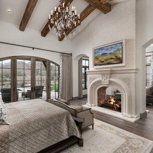 Ejemplo de dormitorio principal, de estilo americano, extra grande, con paredes blancas, suelo de madera oscura, chimenea de doble cara, marco de chimenea de piedra y suelo marrón