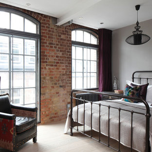 Design ideas for a medium sized industrial guest bedroom in London with grey walls.