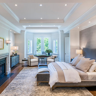 Inspiration for a transitional master medium tone wood floor, tray ceiling and wallpaper bedroom remodel in Boston with white walls, a standard fireplace and a stone fireplace