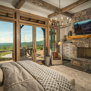 Inspiration for a rustic guest brown floor bedroom remodel in Charlotte with white walls, a standard fireplace and a stone fireplace