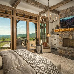 Imagen de habitación de invitados rústica con paredes blancas, chimenea tradicional, marco de chimenea de piedra y suelo marrón