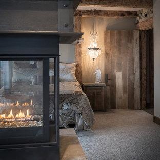 Foto de dormitorio principal, rural, grande, con paredes marrones, moqueta, chimeneas suspendidas y marco de chimenea de metal