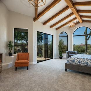 Diseño de dormitorio principal, de estilo americano, con paredes blancas, moqueta, chimenea de esquina, marco de chimenea de yeso y suelo gris