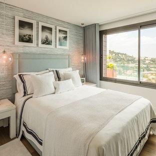Idée de décoration pour une chambre parentale tradition de taille moyenne avec un sol en bois clair, aucune cheminée et un mur gris.