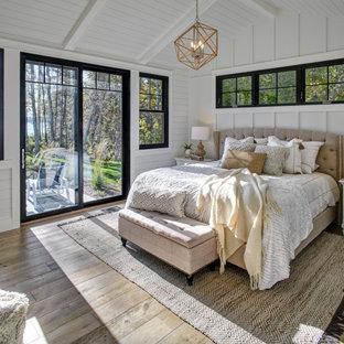 他の地域の中くらいのビーチスタイルのおしゃれな主寝室 (白い壁、無垢フローリング、茶色い床、表し梁、塗装板張りの天井、三角天井、パネル壁、塗装板張りの壁) のレイアウト