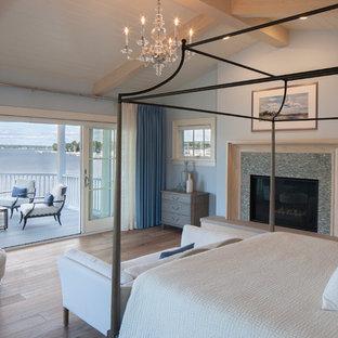 Modelo de dormitorio tipo loft, costero, extra grande, con paredes azules, suelo de madera clara, chimenea tradicional, marco de chimenea de baldosas y/o azulejos y suelo marrón