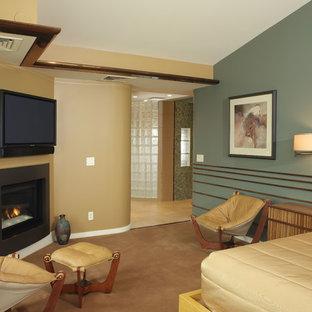 Ejemplo de dormitorio principal, moderno, grande, con paredes verdes, moqueta, chimenea de esquina y marco de chimenea de metal