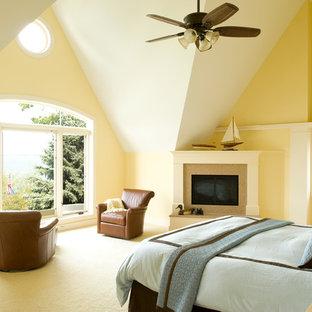 Diseño de habitación de invitados grande con paredes amarillas, moqueta, chimenea tradicional y marco de chimenea de piedra