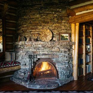 Modelo de dormitorio principal, rústico, grande, con suelo de madera en tonos medios, chimenea de esquina y marco de chimenea de piedra