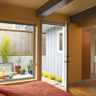 シアトルの中くらいのミッドセンチュリースタイルのおしゃれな客用寝室 (黄色い壁、無垢フローリング、暖炉なし)