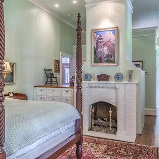 Idee per una camera matrimoniale country di medie dimensioni con pareti verdi, pavimento in legno massello medio, camino classico e cornice del camino in mattoni