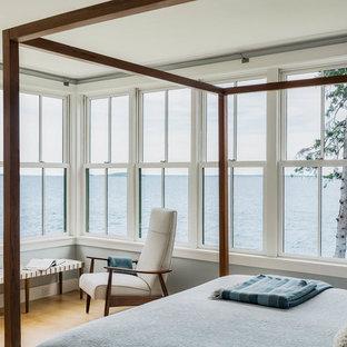 Ejemplo de dormitorio principal, costero, grande, con paredes azules y suelo de madera clara