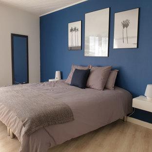 Imagen de dormitorio principal y machihembrado, contemporáneo, grande, sin chimenea, con paredes azules, suelo de madera clara y suelo beige