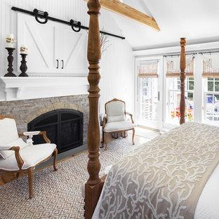 ボストンの広いビーチスタイルのおしゃれな主寝室 (白い壁、標準型暖炉、石材の暖炉まわり、濃色無垢フローリング、茶色い床)