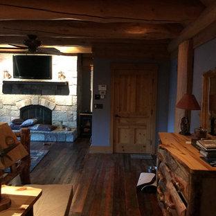 Cette photo montre une chambre chic en bois de taille moyenne avec un mur bleu, un sol en bois foncé, un poêle à bois, un manteau de cheminée en pierre de parement, un sol marron et un plafond en poutres apparentes.