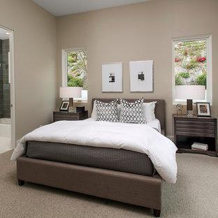Immagine di una grande camera matrimoniale minimalista con pareti beige, moquette, camino classico, cornice del camino in pietra e pavimento beige