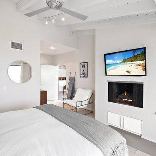 Modelo de dormitorio principal, costero, de tamaño medio, con paredes grises, suelo de piedra caliza, chimenea tradicional, marco de chimenea de yeso y suelo beige