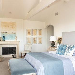 Imagen de dormitorio principal, costero, grande, con paredes blancas, moqueta, chimenea tradicional y marco de chimenea de yeso