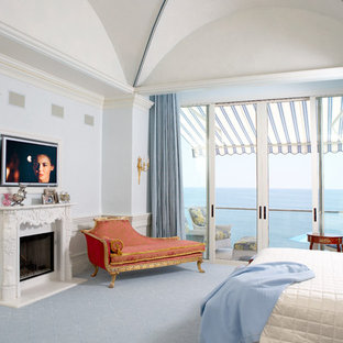 Design ideas for a large traditional master bedroom in Los Angeles with blue walls, carpet, a standard fireplace and blue floor.