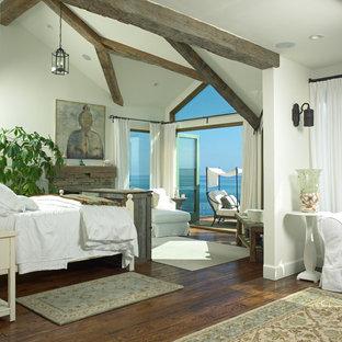 Diseño de dormitorio principal, costero, grande, con suelo de madera oscura, chimenea tradicional, marco de chimenea de piedra, suelo marrón y paredes blancas
