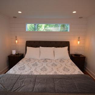 Modelo de dormitorio principal, de estilo americano, de tamaño medio, con paredes blancas, suelo de bambú y suelo rojo