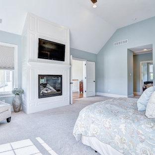 フィラデルフィアの巨大なトラディショナルスタイルのおしゃれな主寝室 (青い壁、カーペット敷き、標準型暖炉、木材の暖炉まわり) のレイアウト