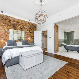 Design ideas for a rustic master bedroom in London with white walls and medium hardwood flooring.