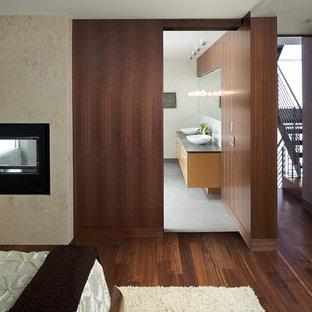 Esempio di una camera da letto minimalista con cornice del camino in pietra e camino bifacciale