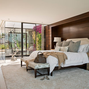 Photo of an expansive beach style master bedroom in Los Angeles with brown walls and light hardwood floors.