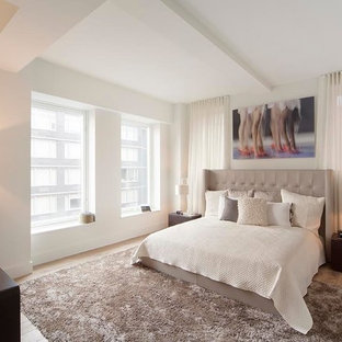 Bedroom - mid-sized contemporary guest medium tone wood floor bedroom idea in New York with white walls