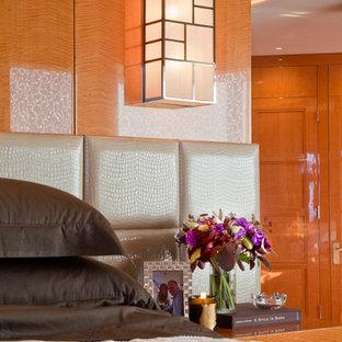 Esempio di una camera matrimoniale design di medie dimensioni con pareti arancioni, pavimento in legno massello medio, camino lineare Ribbon e cornice del camino in metallo