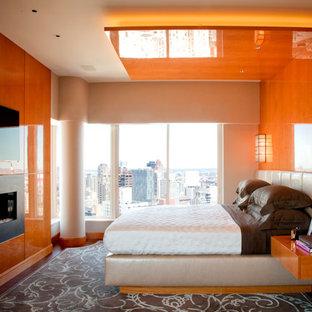 Esempio di una camera matrimoniale contemporanea di medie dimensioni con pareti arancioni, pavimento in legno massello medio, camino lineare Ribbon e cornice del camino in metallo