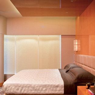 Imagen de dormitorio principal, contemporáneo, de tamaño medio, con parades naranjas, suelo de madera en tonos medios, chimenea lineal y marco de chimenea de metal