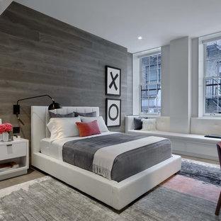 Large trendy guest light wood floor and gray floor bedroom photo in New York with gray walls