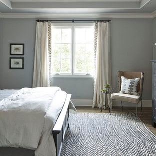 Mid-sized farmhouse guest medium tone wood floor bedroom photo in Atlanta with gray walls and no fireplace