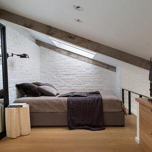 Inspiration för små industriella sovloft, med vita väggar och ljust trägolv