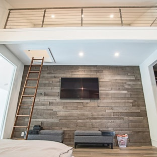 Mid-sized contemporary loft-style bedroom in Miami with white walls, light hardwood floors, no fireplace and brown floor.