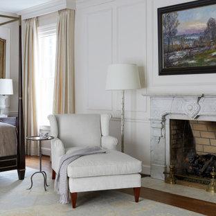 Идея дизайна: большая хозяйская спальня в классическом стиле с белыми стенами, паркетным полом среднего тона, стандартным камином, фасадом камина из камня, коричневым полом и панелями на части стены