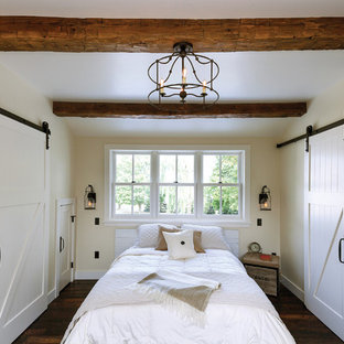 Bedroom - farmhouse dark wood floor bedroom idea in Other with beige walls and no fireplace